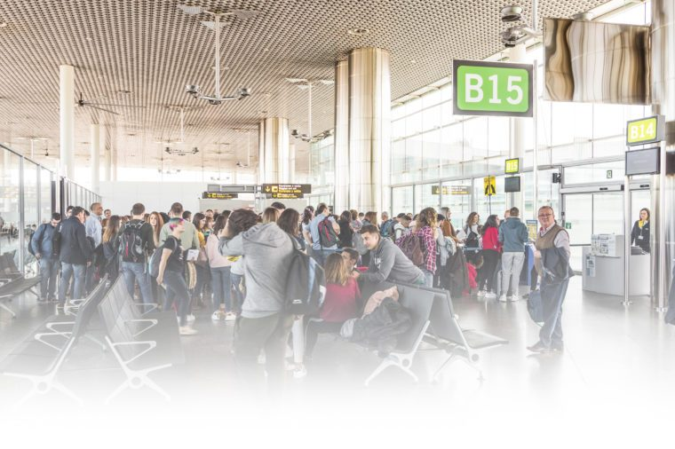 people crowding around an airport gate