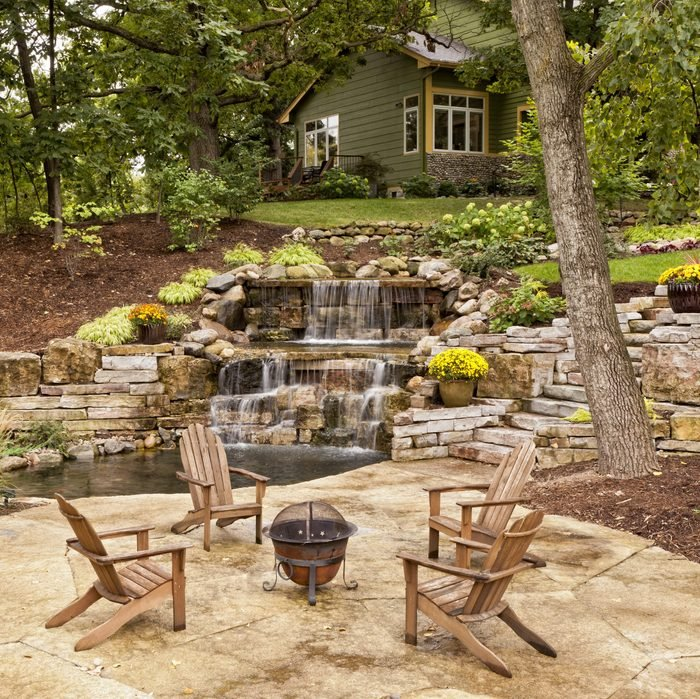 Beautiful landscaping with waterfall, koi pond, and stone patio with wooded surroundings.