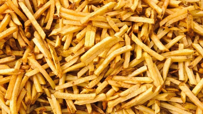 Background of cooked french fries just pulled from the deep fryer.