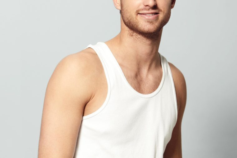 anonymous man in a white tank top. gray background