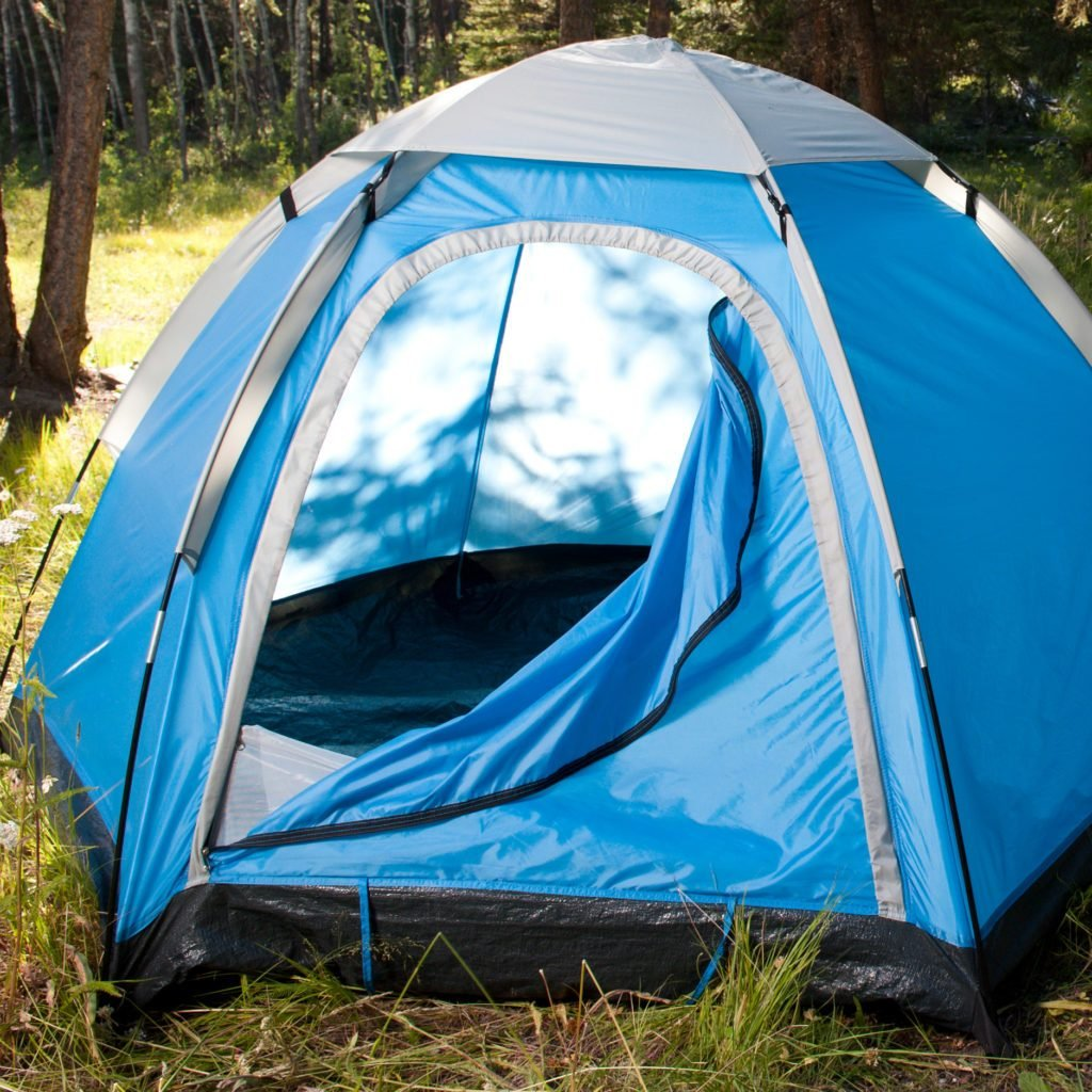 blue camping tent in the woods with door flap open