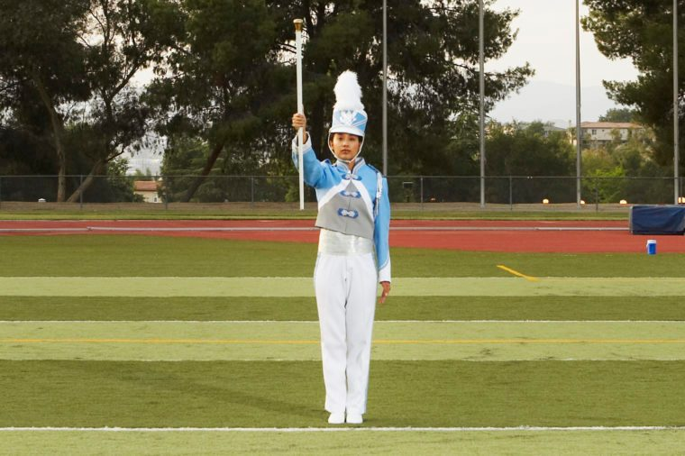 Female marching band member in full uniform on football field
