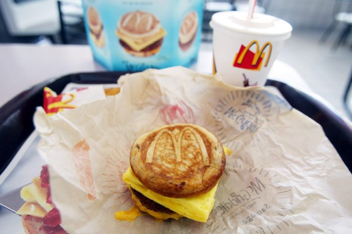 a sausage egg and cheese mcgriddle breakfast on a try with drink in a mcdonalds restaurant
