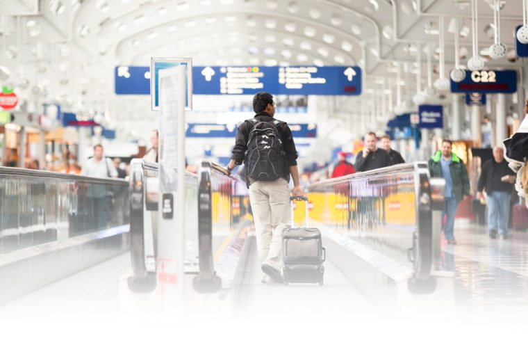Passenger walking through Chicago O'Hare International Airport on moving sidewalk