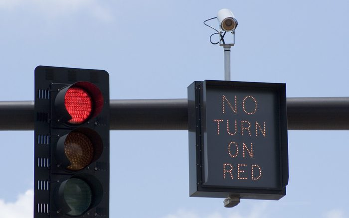 """Red traffic light camera with """"No Turn On Red"""" sign and intersection camera."""