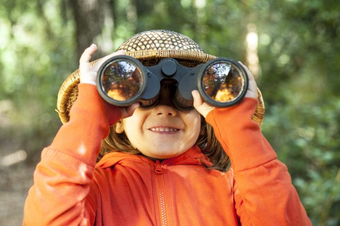 Six years old girl close up, looking through binoculars.