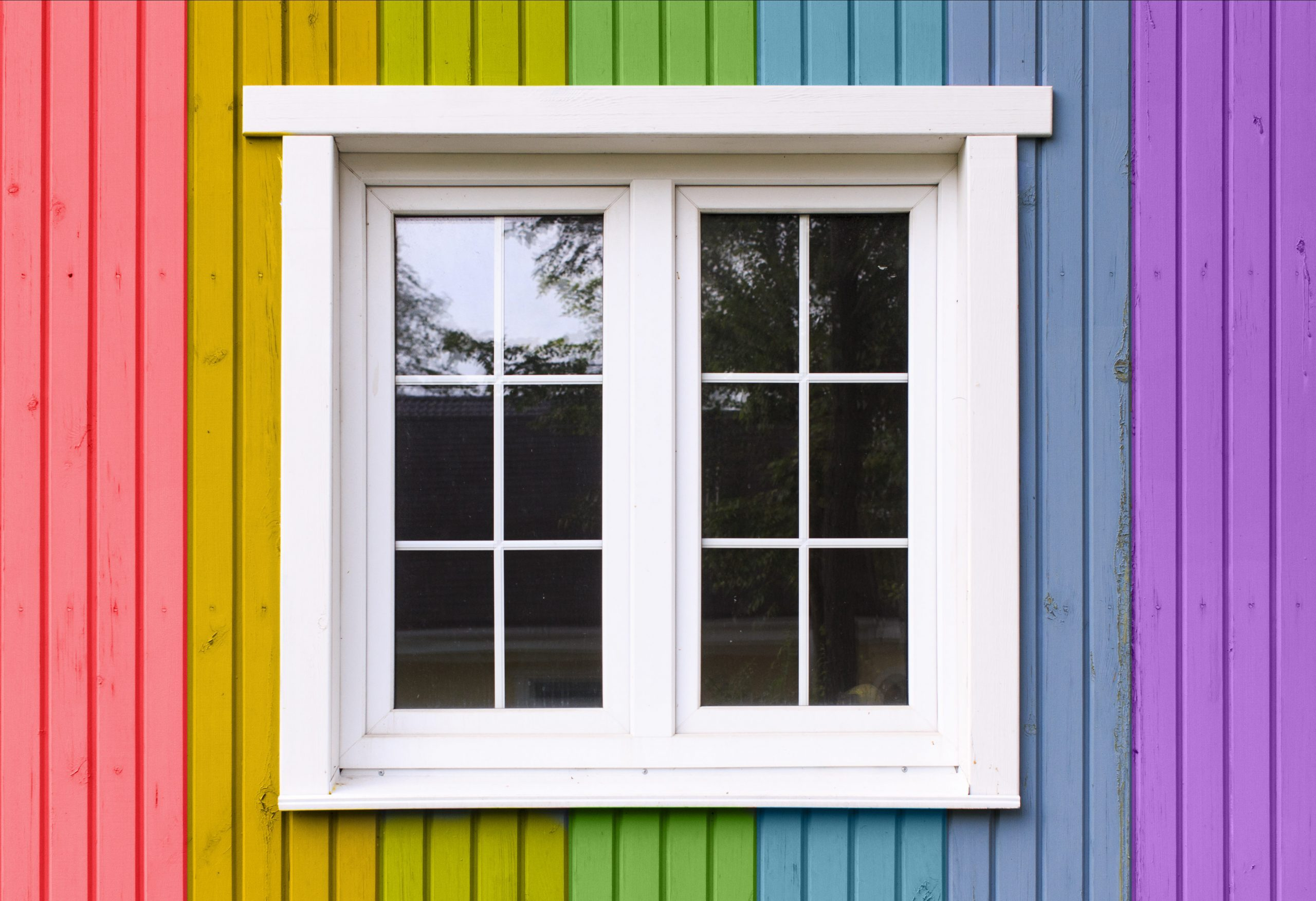 wooden wall of a house painted in a rainbow of colors