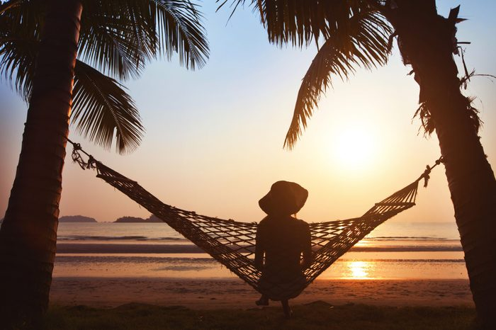silhouette of a woman relaxing in hammock at sunset on the beach