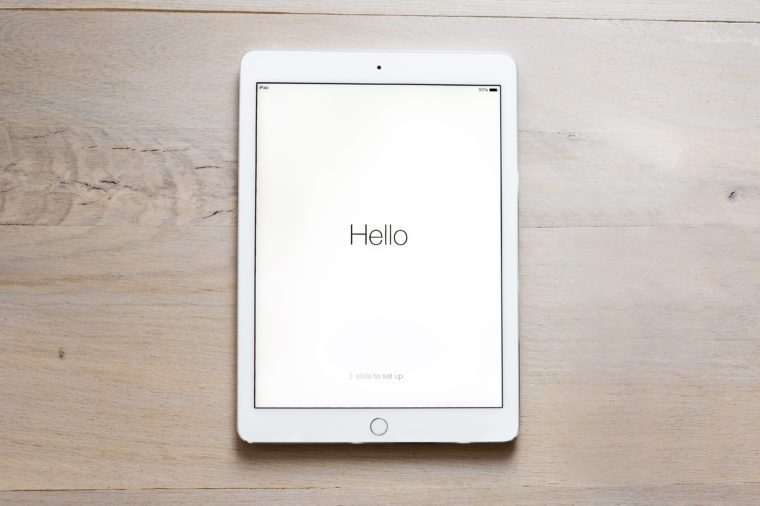 """iPad Air 2 on wood table. says, """"Hello"""" on the screen."""