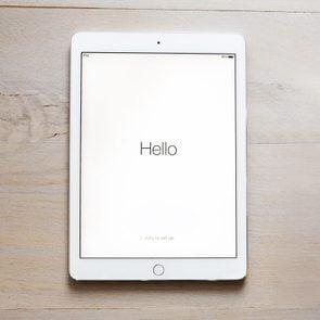 iPad Air 2 on wood table. says,