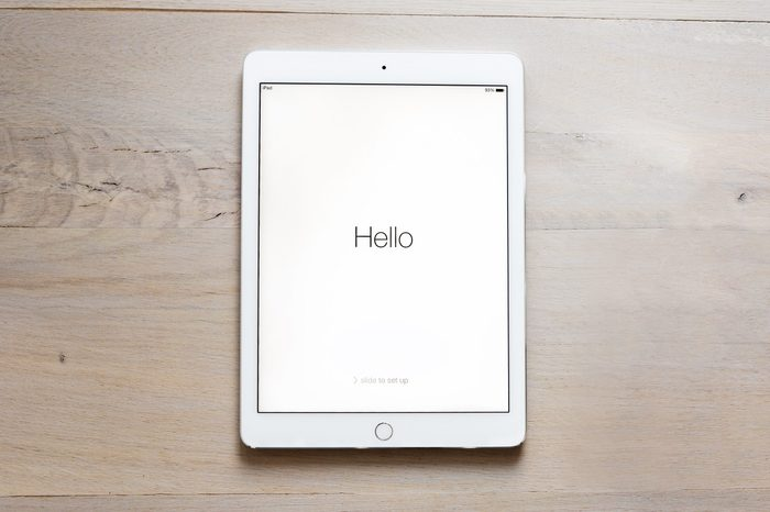"iPad Air 2 on wood table. says, ""Hello"" on the screen."
