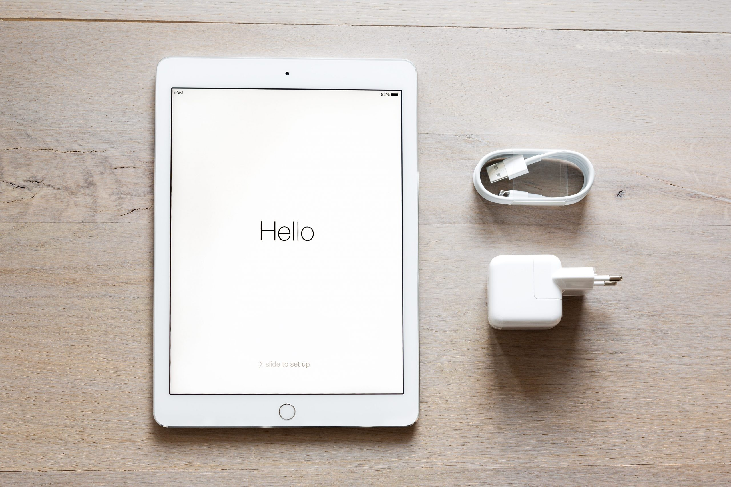 Overhead shot of an iPad Air 2 Silver showing welcome screen, USB cable and power adapter. Unboxed new iPad Air 2 (before activation) on a wooden background.