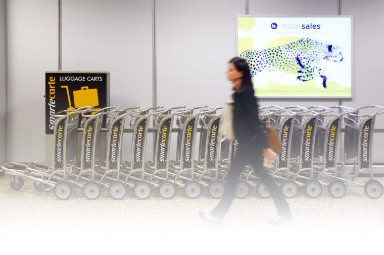 An airplane passenger walks past a Smarte Carte vending station at Salt Lake City International Airport in Salt Lake City, Utah.