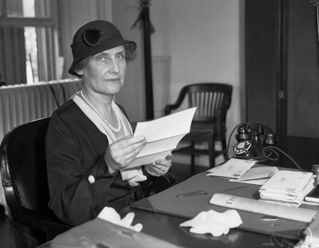 First Woman Director Of The U. S. Mint. Mrs. Nellie Tayloe Ross, former Governor of Wyoming, seated at her desk in the U. S. Treasury Building as she assumes her new duties as Director of the Mint.