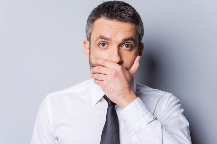 man in a shirt and tie covering his mouth with one hand. gray background.