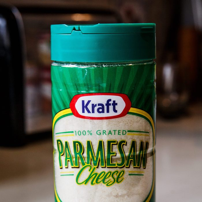 Kraft Parmesan Cheese brand in plastic shaker container. Prepared 100% grated Parmesan cheese in green packaging ready to sprinkle on food dishes.