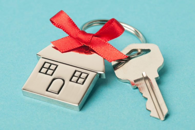 key and house keychain with red bow on aqua background