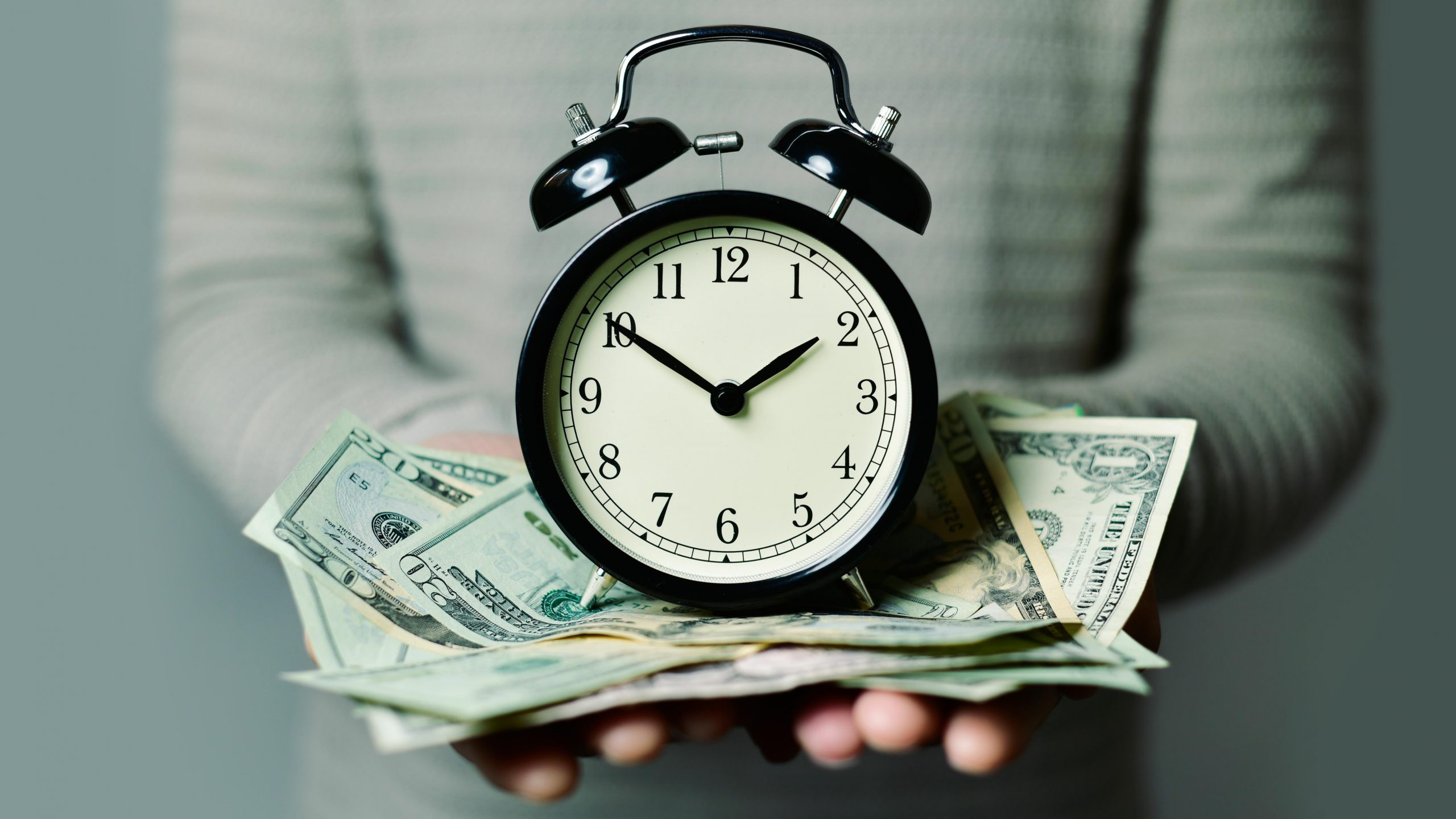 close up of a person holding an alarm clock sitting on US bills in the person's hands