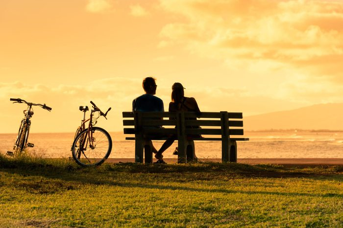 Silhouette couple sitting on park bench watching the beautiful sunset in Hawaii.