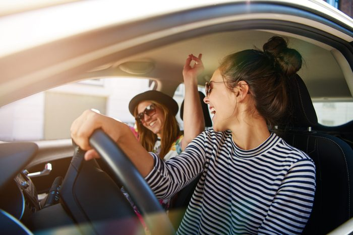 Two young women having fun driving along the street singing and laughing