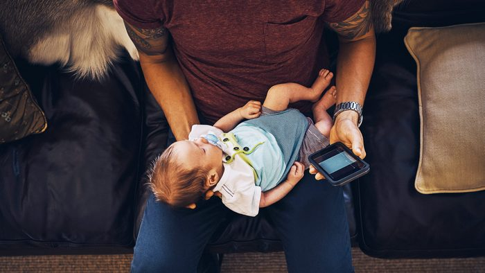 young man using a mobile phone while holding his newborn baby boy at home