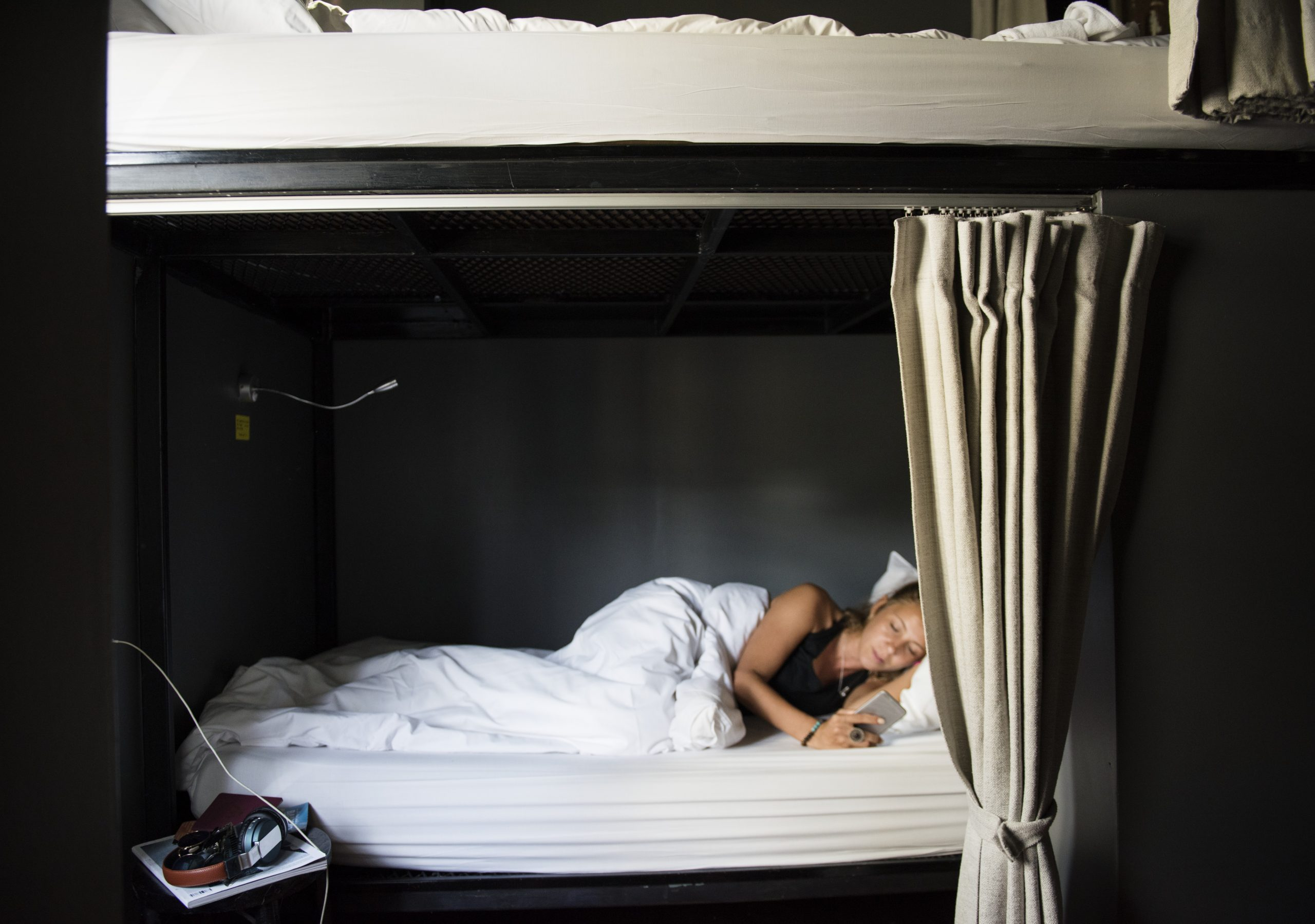 woman lying on hostel bed using mobile phone
