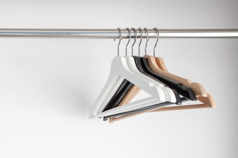 Wooden hangers on white wall background