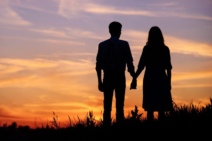 couple holding hands on a background sunset silhouette.