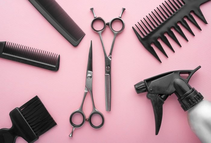 Professional hairdresser tools top view. on pink background.
