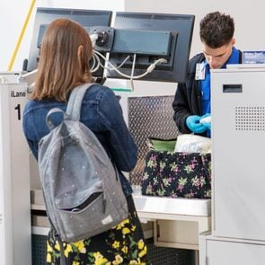 woman watching as a tsa agent searches her bag