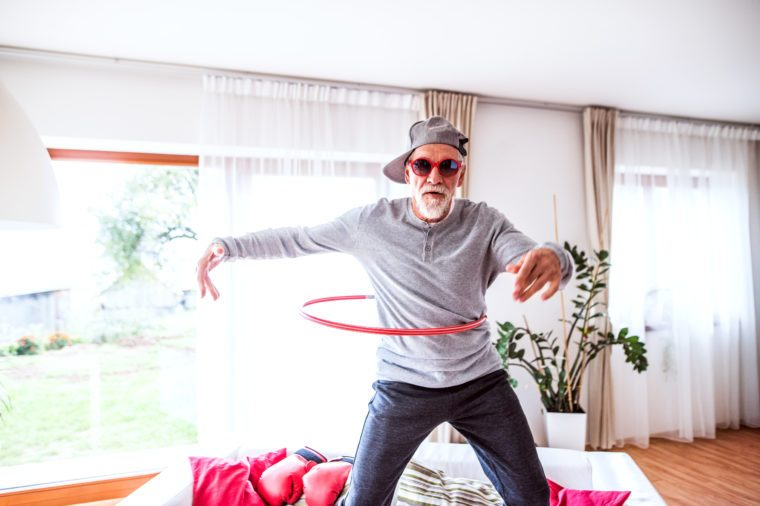 senior man using a hula hoop while standing on the couch in his home.