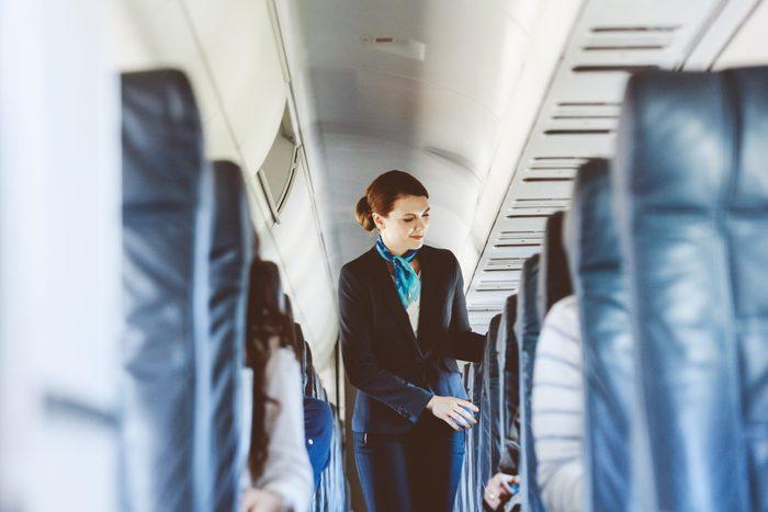 Beautiful air stewardess inside an airplane