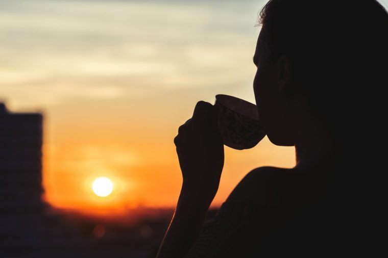 Silhouette of girl with a cup of tea at sunset.