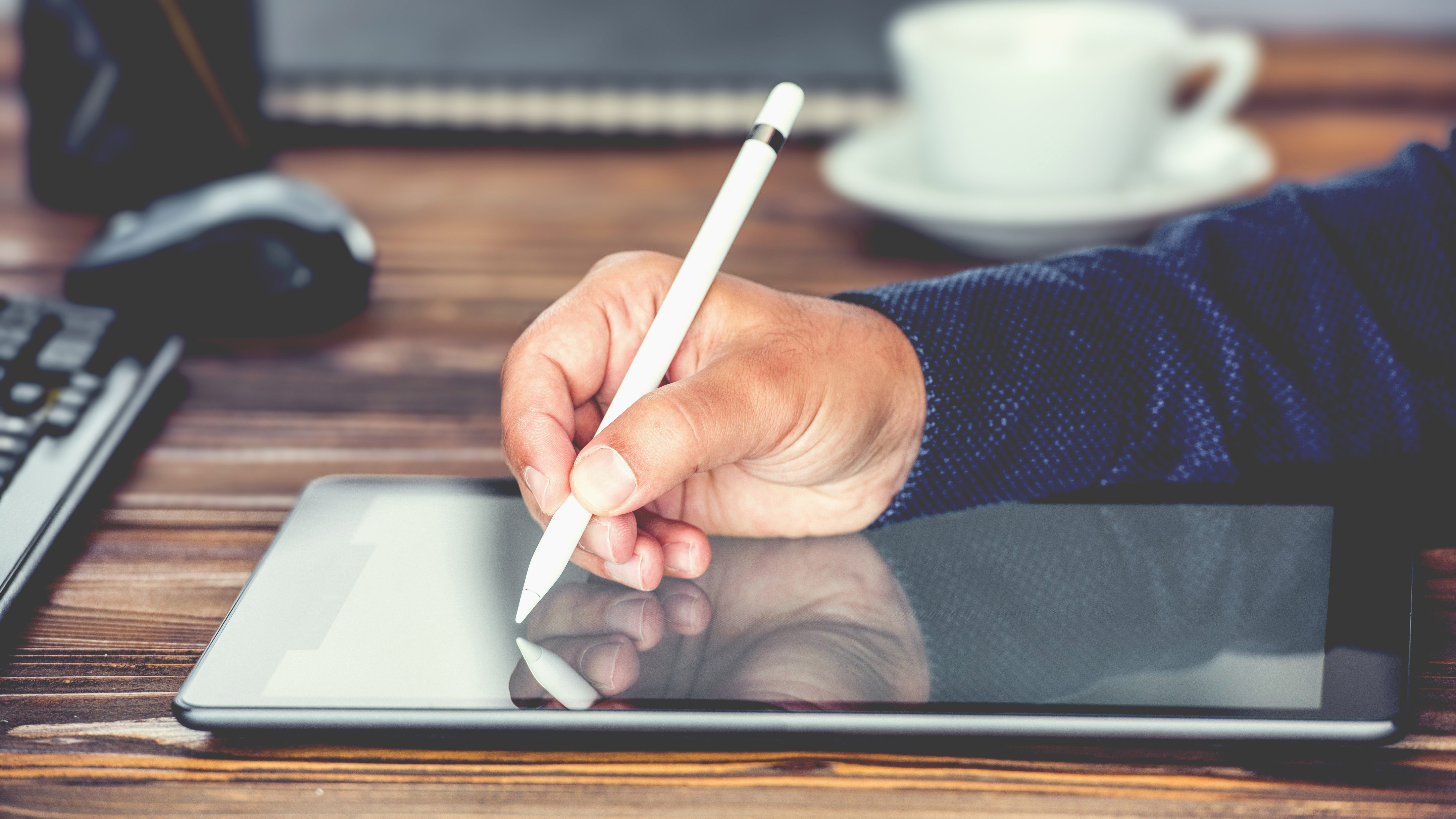 man signing on a tablet with a stylus pen at a wooden desk