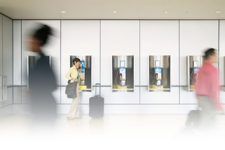 people walk past as a woman used a payphone at an airport