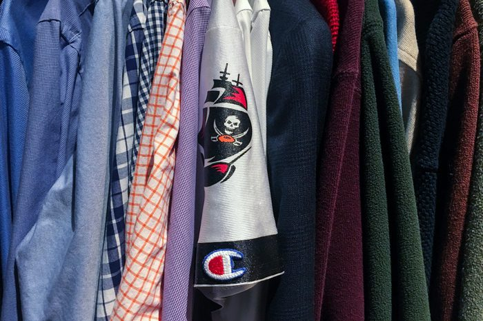 sports fan jersey mixed in with other clothes in a closet
