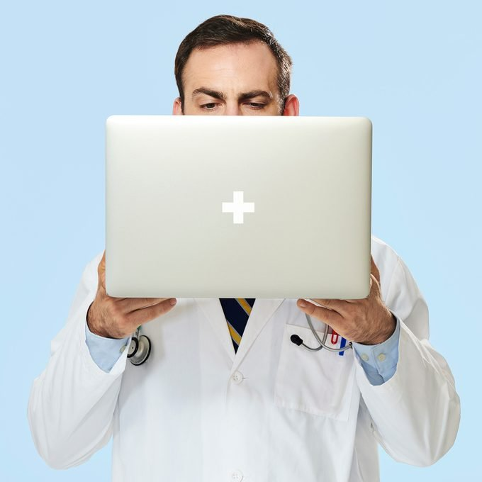 doctor holding laptop in front of his face. blue background
