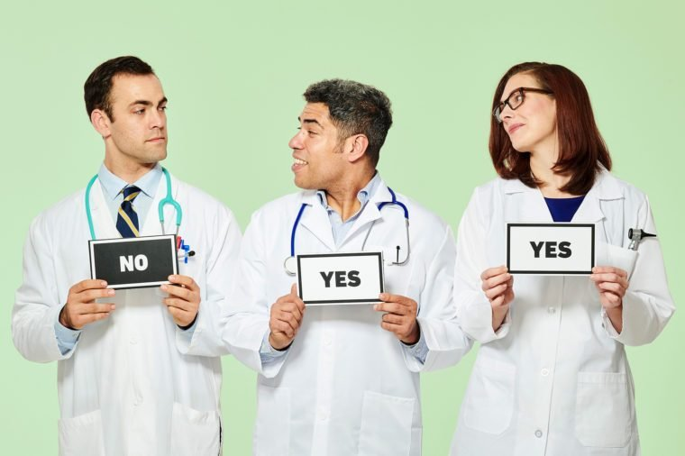 """three doctors standing a row. one holds """"no"""" sign, other two hold """"yes"""" signs. green background"""
