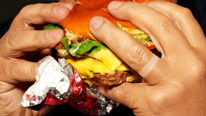 close up of man eating a fast food burger with wedding ring tan