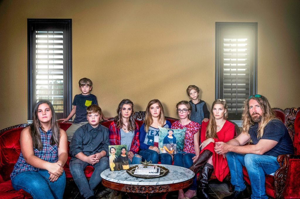 The Cogburn family on the couch holding pillows with images of sabika