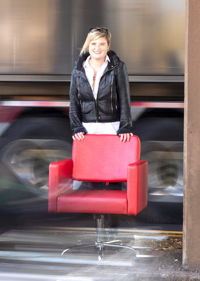 Katie Stellar and her red barber's chair amidst traffic.