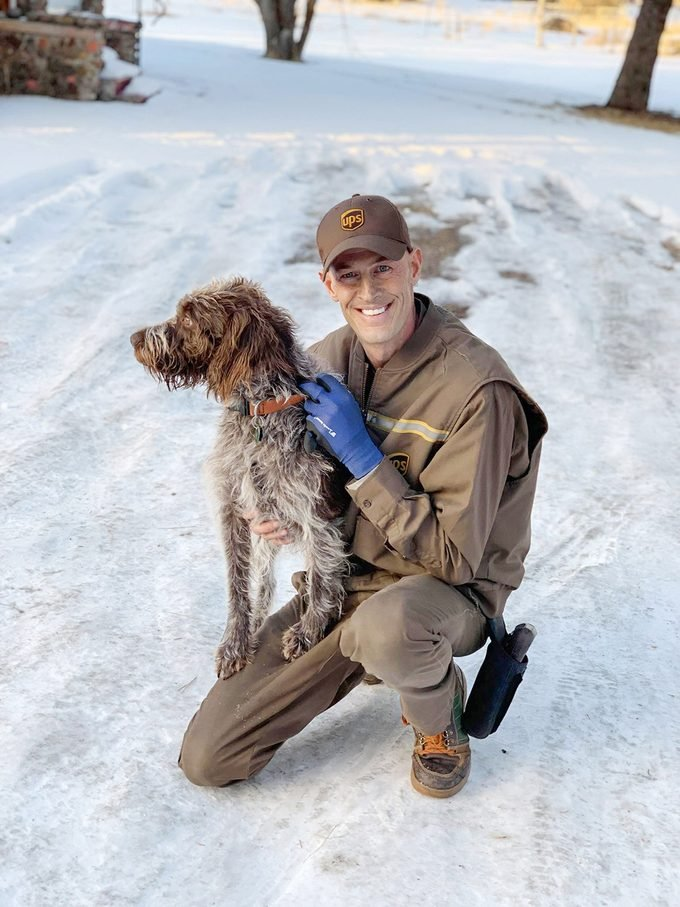 Ryan Arens, in his UPS uniform, and dog