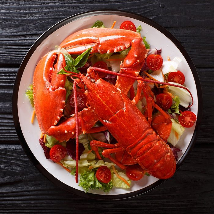 Cooked sea lobster with fresh vegetable salad on a plate close-up on the table. Vertical top view from above