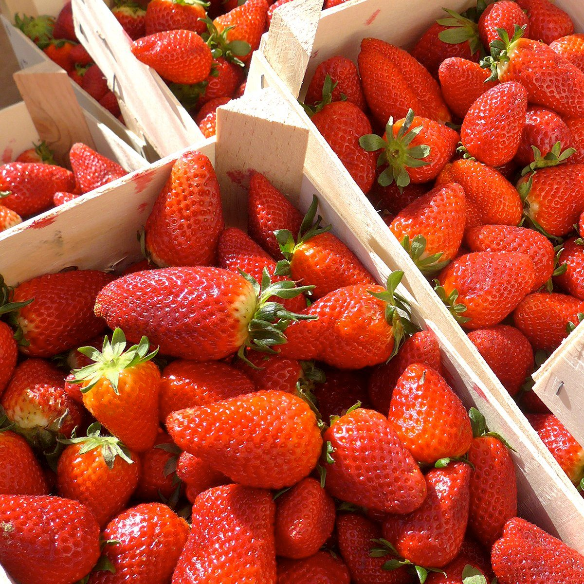 Fresh strawberries in wooden boxes, ready for sale.