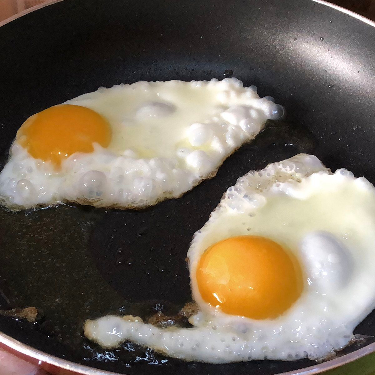Photo showing two fried eggs that are being cooked in a greasy frying pan, as part of a full-English fried breakfast fry-up.