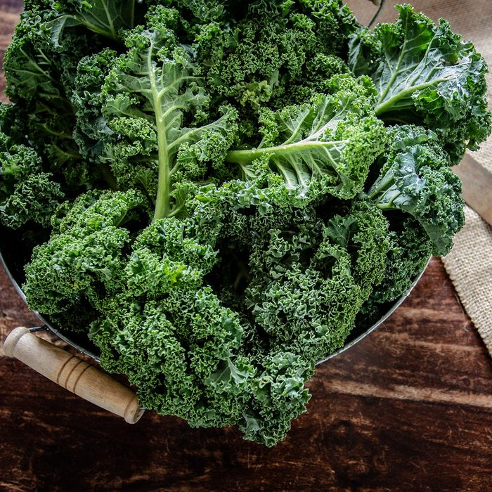 Green Kale in basket and knife on wooden background top view on daylight superfood vegetables Still life