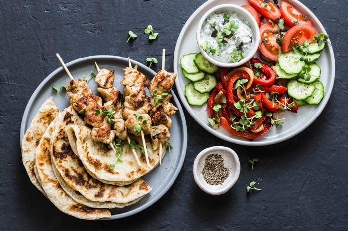Mediterranean style lunch table - turkey skewers, flatbread, tomatoes, cucumber salad, baked sweet pepper, yogurt herb sauce on a dark background, top view