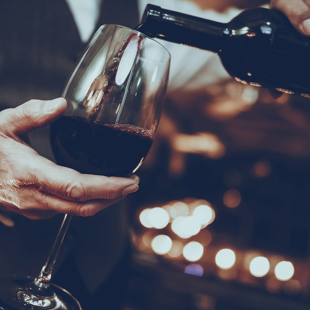 Experienced Sommelier is Working in Restaurant. Sommelier is Pouring Wine from Bottle to Glass. Red Wine. Sommelier is Caucasian Man. Person is Wearing Special Uniform. Closeup View.