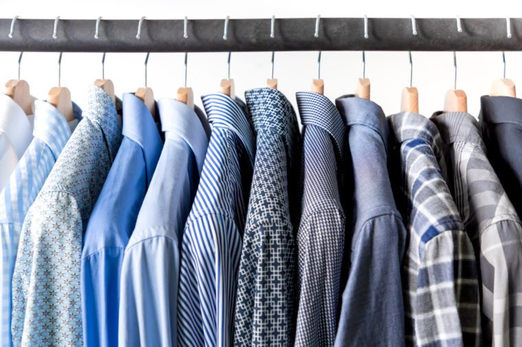 Row of men's shirts in blue colors on hanger on white background