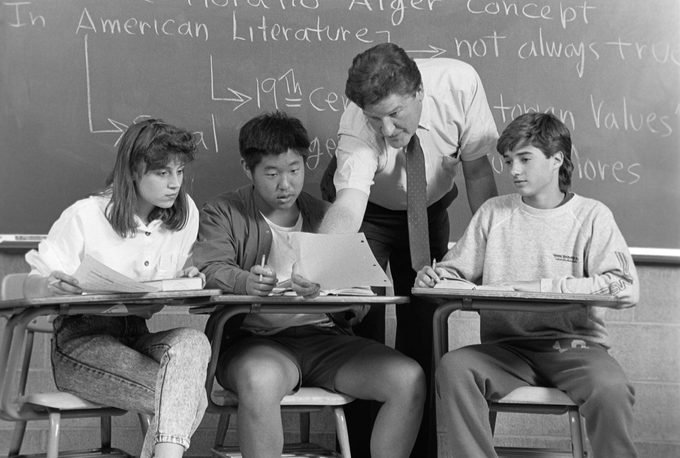 1980s COLLEGE STUDENTS TEACHER IN CLASSROOM SITTING AT DESKS TEACHER LEANING OVER DESK EXAMINING PAPER OF STUDENT